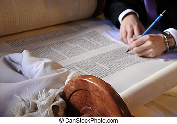 Sofer completing the final letters of sefer Torah - A sofer...