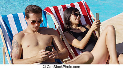 Young couple using phones at the swimming pool - Young...