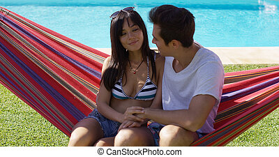 Loving young couple sitting on a hammock near a swimming...