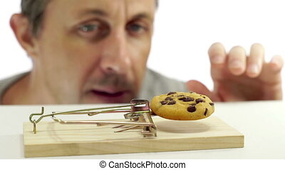 Man Looking at Cookie In Rat Trap - Close up shot of a man...