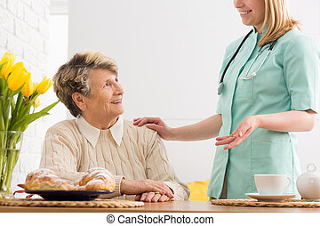 How can I help you - Senior woman sitting at a wooden table...