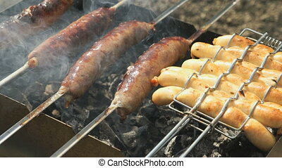 Frying of sausages on the grill and the skewers - Frying of...