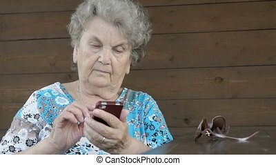 Old woman holding a smartphone sits outdoors