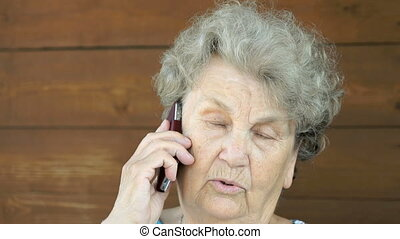 Old woman talking on the smartphone phone - Old woman...