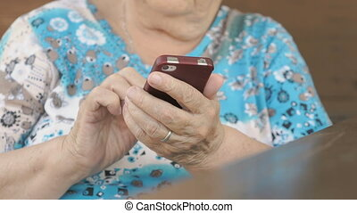 Woman sitting at the table holds a smartphone