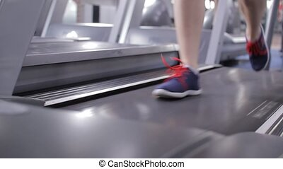 Legs of young strong girl running on treadmill in gym