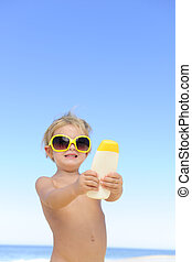 cute child showing suncream - child showing suncream at the...