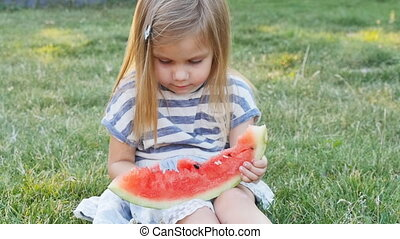 cute little girl eating watermelon on the grass in...