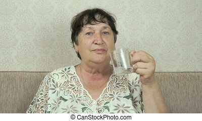 Elderly woman smiles, drinks water, shows thumb up - The...