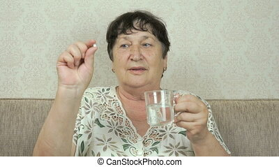 Old woman takes pill, drinks the water from glass