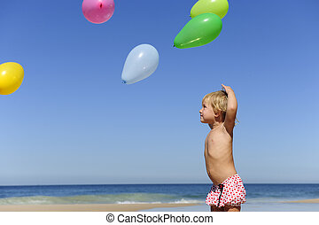Child with ballons on the beach