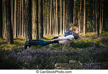 Beautiful blond girl levitates in the forest.