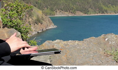 Girl sitting on the shore of Lake Baikal on a rock and using a tablet