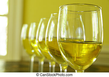 closeup of white wine glasses in a row