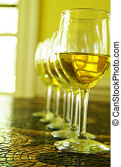 white wine glasses in a row, on tile table