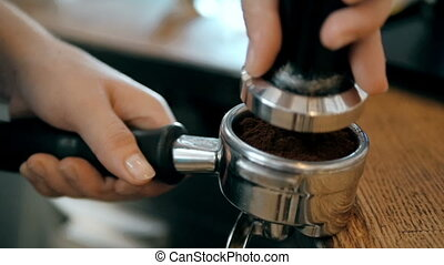 Barista Hands Using a Tamper To Press Freshly Ground Coffee...