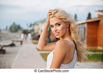 Happy charming young woman standing outdoors - Portrait of...