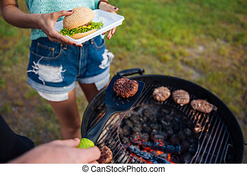 People cooking meet on barbeque grill and making hamburger outdoors