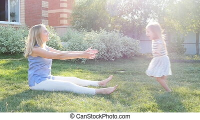 Young mum embraces a daughter on the lawn sunset