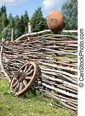 old broken wooden carriage wheel on wattled fence and pot...