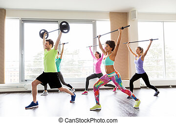 happy people exercising with barbell bars in gym