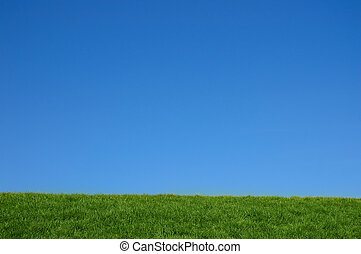 Green grassy hill and bright blue sky