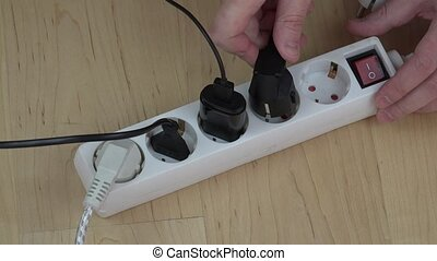 man hands insert wire plugs and turn on extension switch on...