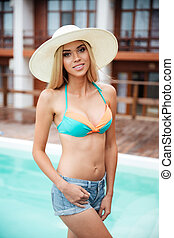Happy charming young woman in hat standing near swiming pool...