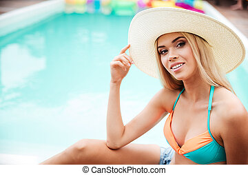 Happy woman in hat sitting near swiming pool - Happy...
