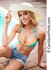 Smiling young woman in hat and shorts near swiming pool -...