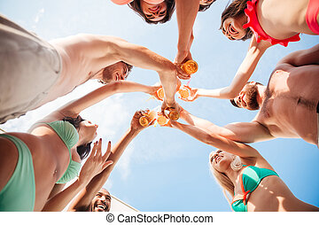Group of friends clinking bottles together - Down view image...