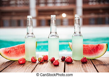 Concept photo alcohol bottles with fresh strawberries halves of watermelon