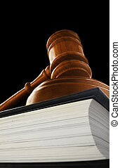 judges court gavel on a law book, on black