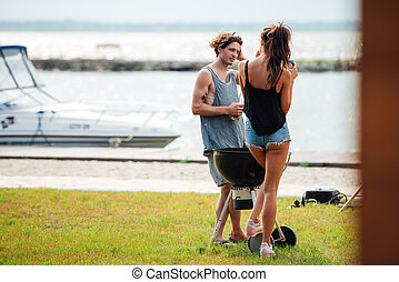 Couple standing and frying meet on barbeque grill outdoors
