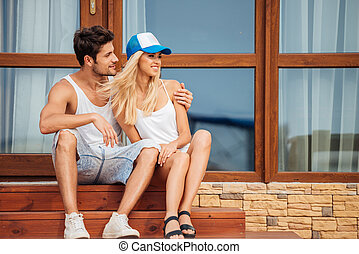 Young beautiful couple sitting on house steps outdoors -...