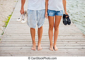 Cropped image of couple walking on the beach holding hands -...