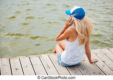 Girl talking on the phone while sitting at the pier - Young...