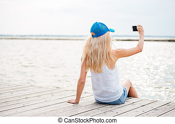 Young blonde girl taking selfie with phone on wooden pier -...