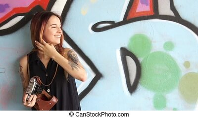 Girl with tattoo stand near the graffiti wall and photographs.