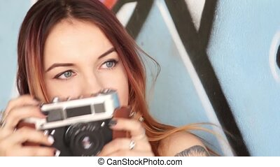 Girl with vintage camera against the graffiti wall and...