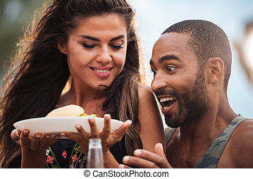 Surprised couple with fresh hamburger outdoors