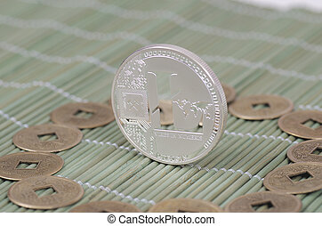 Litecoin - Silver-plated Litecoin on a wooden tablecloth....