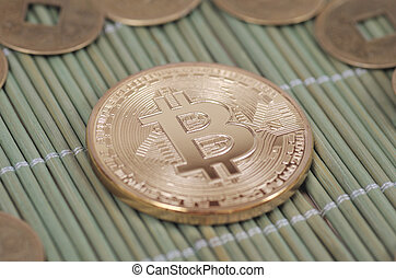 Bitcoin - Gold-plated Bitcoin on a wooden tablecloth....