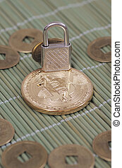 Bitcoin - Gold-plated Bitcoin and padlock on a wooden...