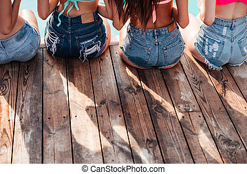 Back view of pretty young girls sitting at pool - Back view...