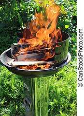 Fire in grill - Charred wood and bright flames on dark...