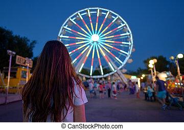 Teen girl  in amusement park at night