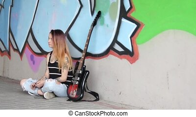 Girl sitting near graffiti wall with a guitar listening...
