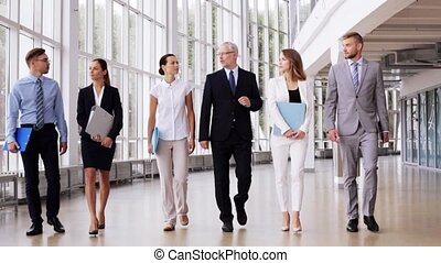 business people walking along office building 7