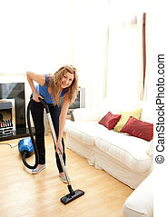 Smiling woman use vacuum cleaner in a living room